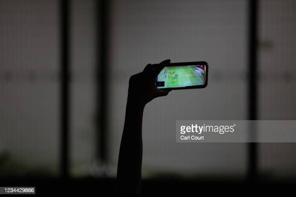 Woman watches Japans mens semi-final match against Spain on a smartphone outside Saitama Stadium where the game is being played without spectators,...