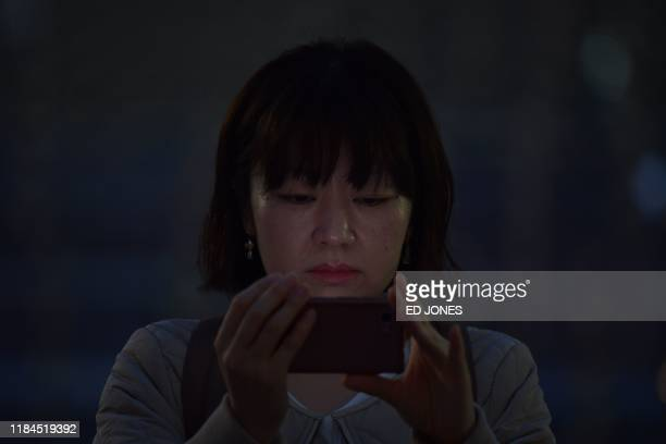A woman watches live video on her mobile phone of Pope Francis leading a holy mass outside the Tokyo Dome stadium in Tokyo on November 25 2019