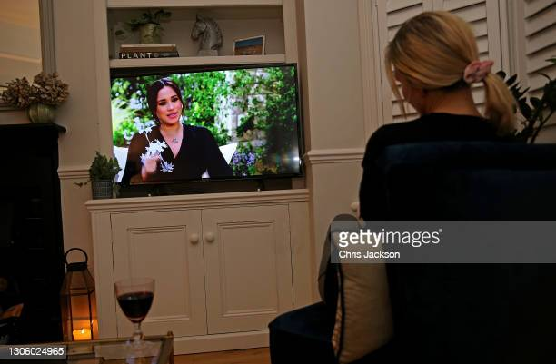 Woman watches Meghan, Duchess of Sussex interviewed by Oprah Winfrey on British Television on March 08, 2020 in London, England. The interview first...