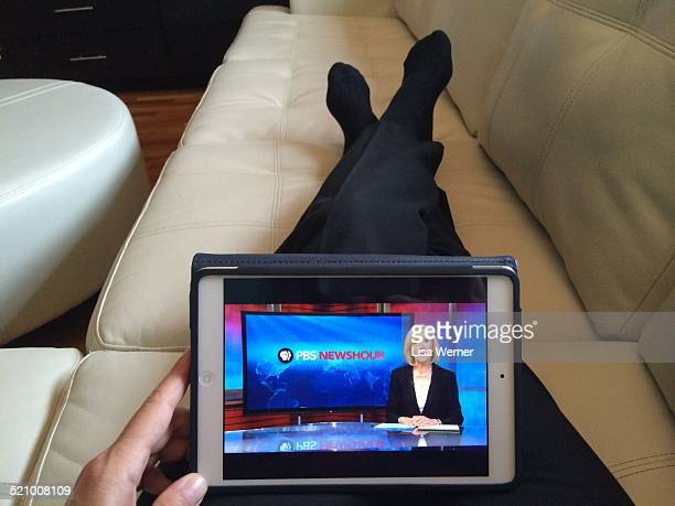 Woman watches news anchor Judy Woodruff on PBS NewsHour via the PBS App on a Mini IPad with Retina Display