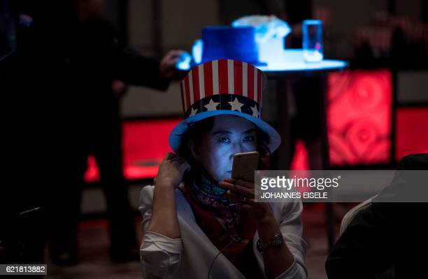 A woman watches news on her smartphone to follow the results of the final day of the US presidential election at an event organised by the American...