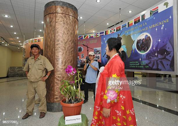 A woman watches North Korean workers taking pictures of themselves in the hall of the 'African Renaissance Monument' on April 2 2010 in Dakar on the...