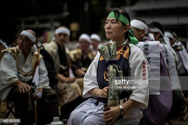 Woman watches on during a Samurai ritual at Nakamura Shrine on July 24, 2015 in Soma, Japan. Every summer the people of Fukushima prefecture have...