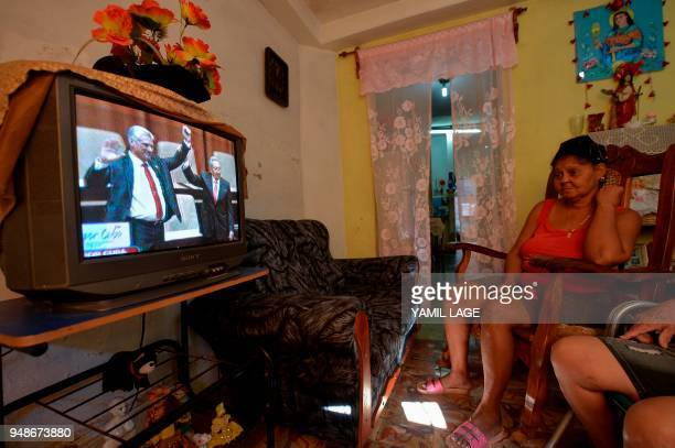 A woman watches on TV at her house in Havana as outgoing Cuban President Raul Castro raises the arm of Cuba's new President Miguel DiazCanel after he...