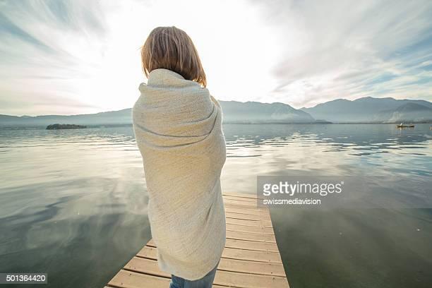 Femme regarde un coucher de soleil depuis la jetée du lac, emmitouflé dans une couverture