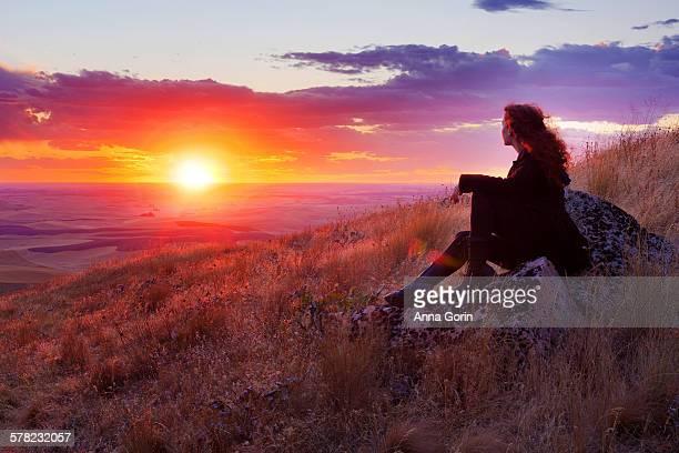 Woman watches sunset over Palouse hills, summer
