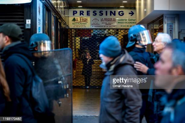 A woman watches the demonstration behind a metal gate barring access to shops during the sixth day of a general strike on December 10 2019 in Paris...