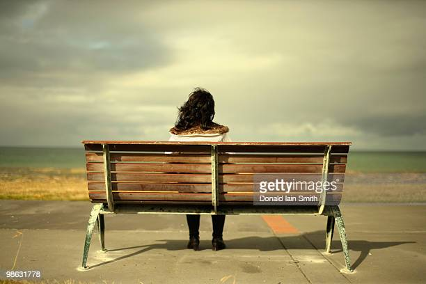 Woman watches the ocean sitting on bench