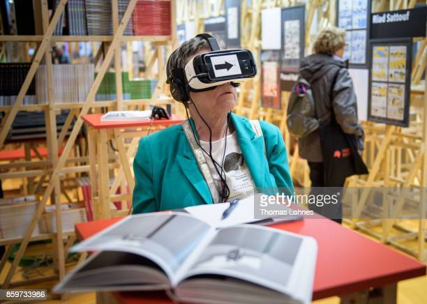 A woman watches the presentation with virtual reality glasses in the French host country exhibition of the 2017 Frankfurt Book Fair on October 10...