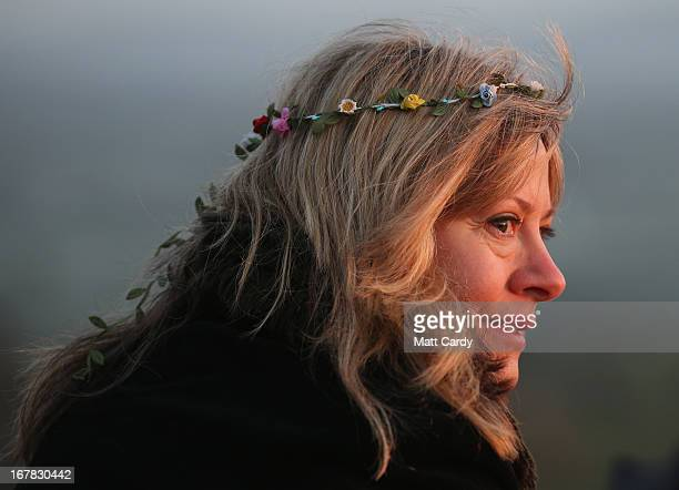 A woman watches the sun rise during a Beltane dawn celebration service in front of St Michael's Tower on Glastonbury Tor on May 1 2013 in Glastonbury...