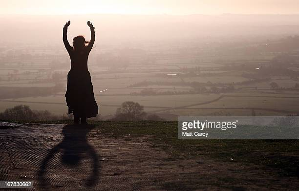 A woman watches the sun rise during Beltane dawn celebration service in front of St Michael's Tower on Glastonbury Tor on May 1 2013 in Glastonbury...