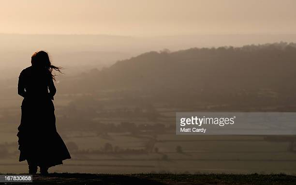 A woman watches the sun rise during the Beltane dawn celebration service in front of St Michael's Tower on Glastonbury Tor on May 1 2013 in...