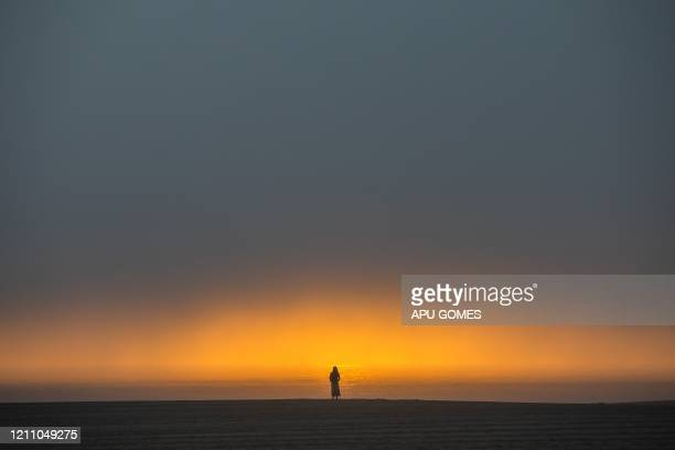 TOPSHOT A woman watches the sunset from the beach in Venice California on April 26 2020 Los Angeles County beaches are still off limits under Los...