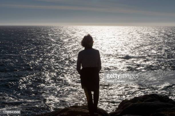 Woman watches the sunset from the cliff surrounding Hercules Tower Lighthouse, as seen July 16 A Coruña, Galicia,Spain.