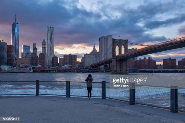 a woman watches the sunset over the new york skyline - lower manhattan stock photos and pictures
