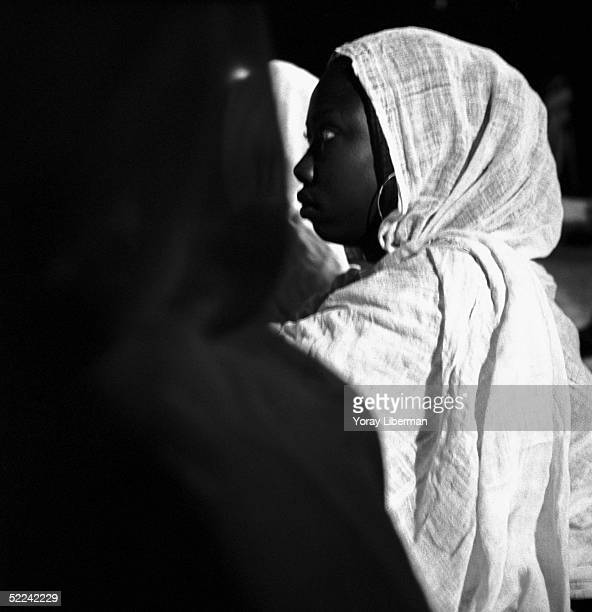 A woman watches the traditional Ziker ritual the night before the Magal De Touba April 22 2003 in Mbake Senegal The Mouride Baye Fall community in...