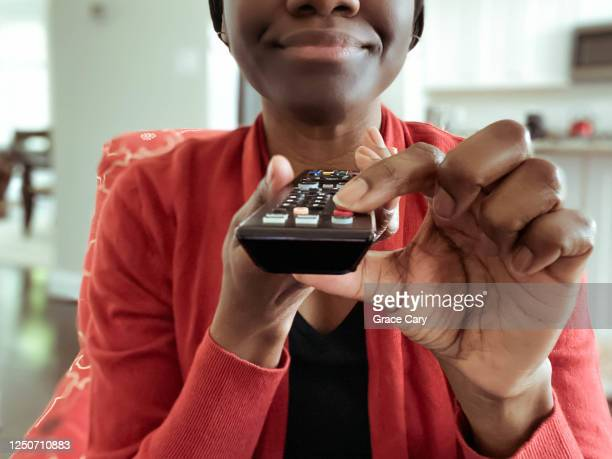 woman watches tv - remote control stock pictures, royalty-free photos & images