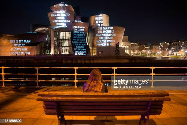 TOPSHOT A woman watches US artist Jenny Holzer's projection mapping creation entitled For Bilbao and projected on the Guggenheim Bilbao Museum's...