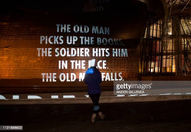A woman watches US artist Jenny Holzer's projection mapping creation entitled 'For Bilbao' and projected on the Guggenheim Bilbao Museum's facade as...