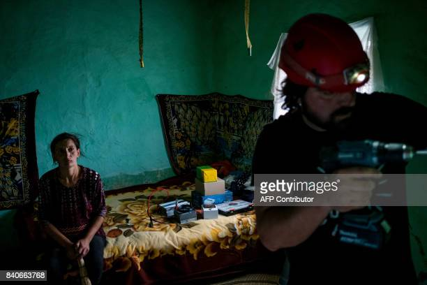 A woman watches while Iulian Angheluta the founder of an NGO that tries to bring electricity to remote villages prepares to install a solar panel on...