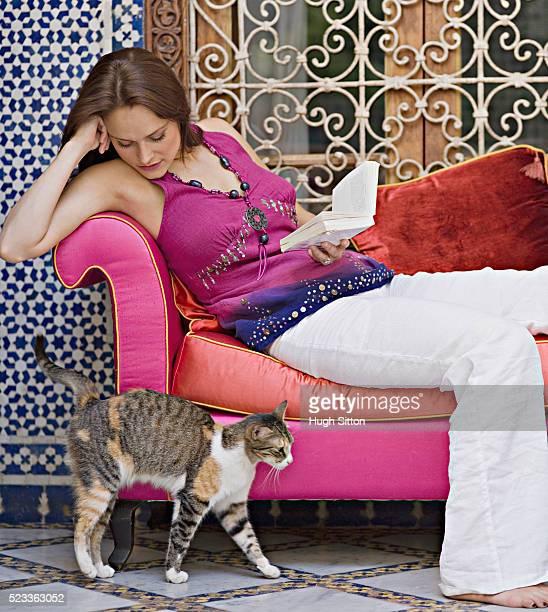 woman watching a cat walking by - hugh sitton bildbanksfoton och bilder