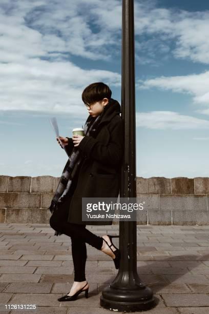 a woman watching a document of work - yusuke nishizawa stock-fotos und bilder