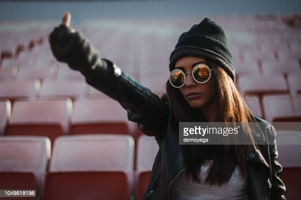 woman watching a game and cheering outdoors - dito medio foto e immagini stock