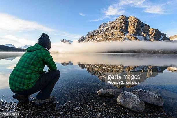 Woman watching a misty sunrise at Bow Lake