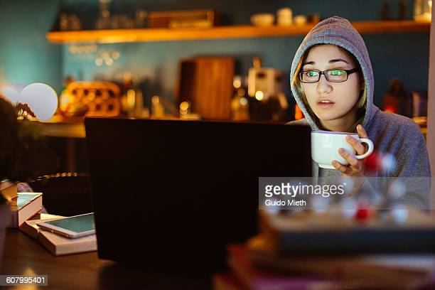 Woman watching a movie at night.