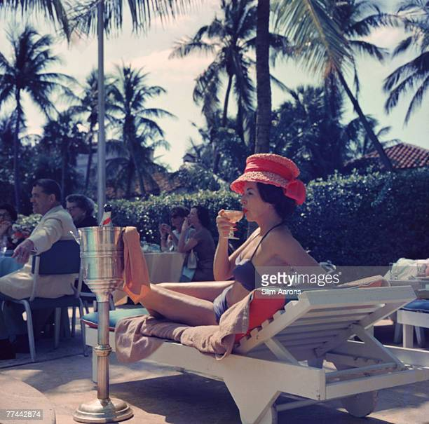 A woman watching a poolside fashion show at the Colony Hotel Palm Beach Florida 1961