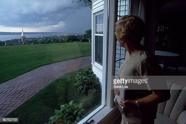 Woman watching approaching storm clouds from her window in town featured in TIME cover story Life on the Mississippi