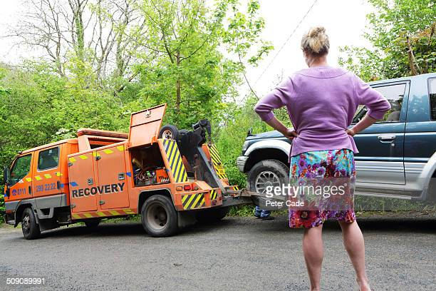 Woman watching as broken down car is towed away