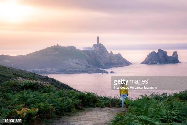 woman watching at faro cabo vilano (cape vilan lighthouse) at sunset, galicia, spain. - comunidad autónoma de galicia fotografías e imágenes de stock