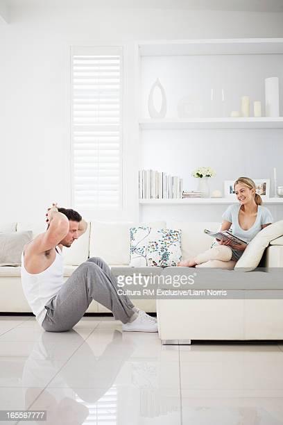Woman watching boyfriend do sit-ups