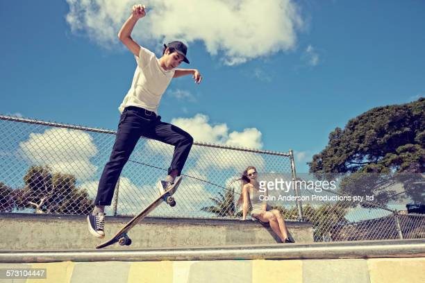 woman watching boyfriend perform trick at skate park - alternative lifestyle stock pictures, royalty-free photos & images