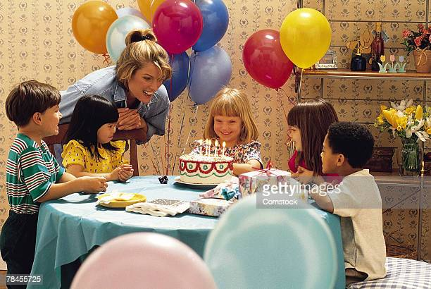 Woman watching children at birthday party