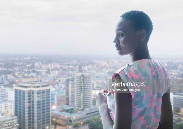 woman watching city from the top of a building - nairobi stock pictures, royalty-free photos & images