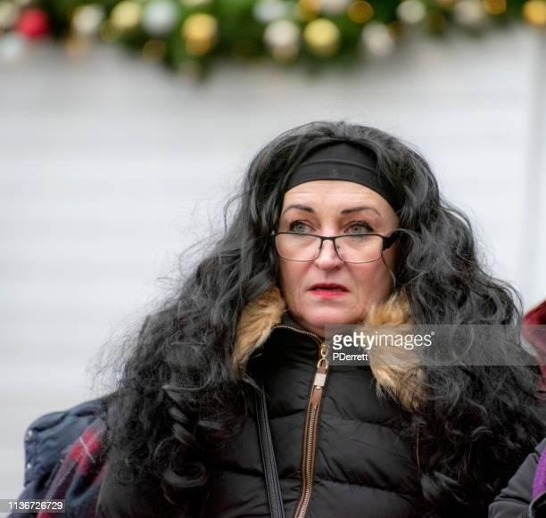 プラハのクリスマスマーケットで祭りを見ている女性。