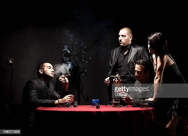 woman watching group of gangster men playing poker - gangster stock pictures, royalty-free photos & images