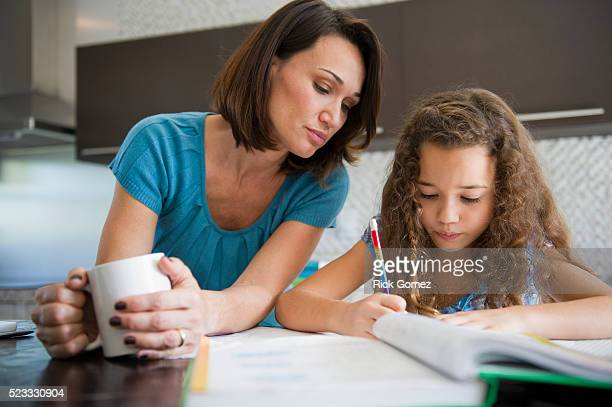 woman watching her daughter do homework - homeschool stock pictures, royalty-free photos & images