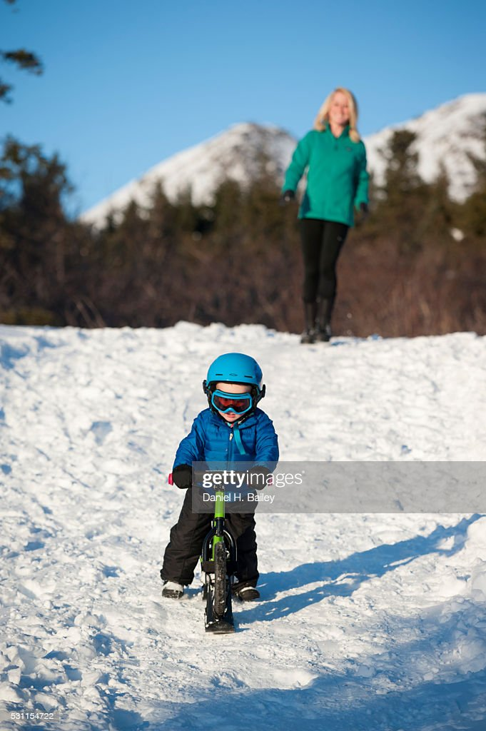 Woman Watching Her Toddler Son Ride A Ski Skoot Bike Down A Snow