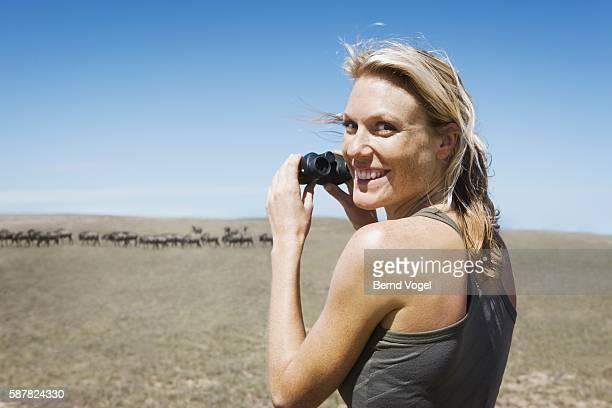 Woman Watching Herd of Wildebeests