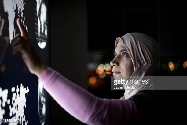 woman watching hologram data - pays du golfe photos et images de collection