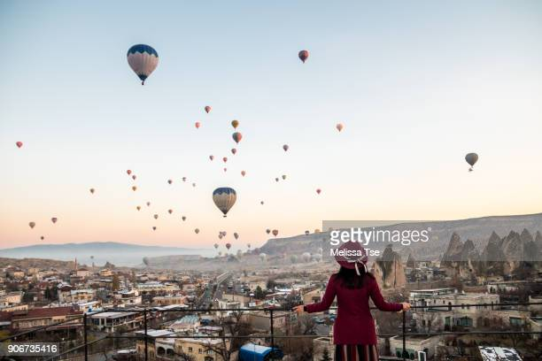 woman watching hot air balloons in cappadocia - tourist stock-fotos und bilder