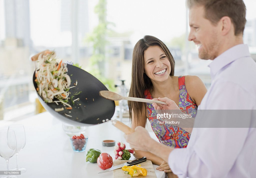 Woman watching husband flipping stirfry in the kitchen : Stock Photo