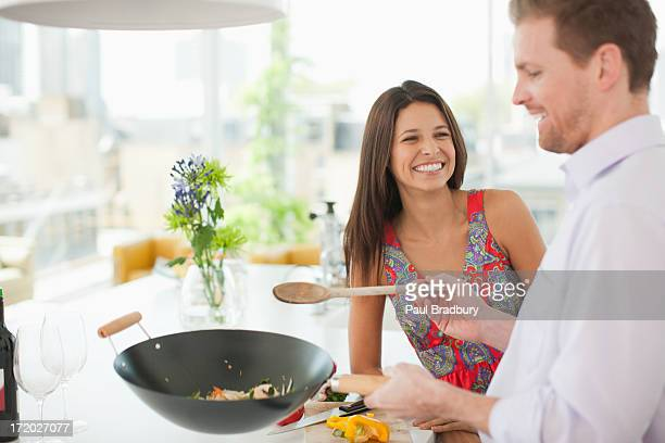 woman watching husband flipping stirfry in the kitchen - food state stock pictures, royalty-free photos & images