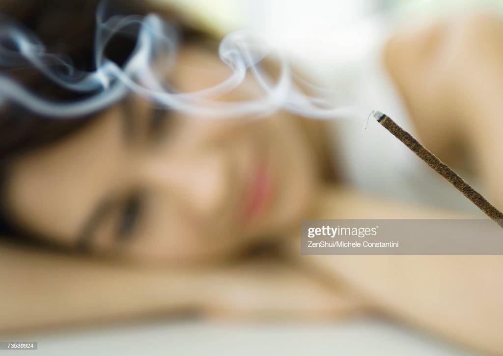 Woman watching incense burn : Foto de stock