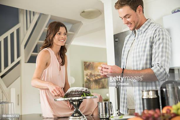 Woman watching man decorate cake