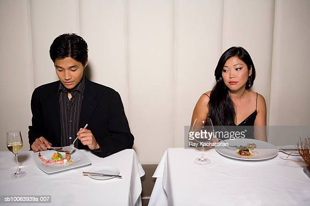 woman watching man eating in restaurant - formal imagens e fotografias de stock