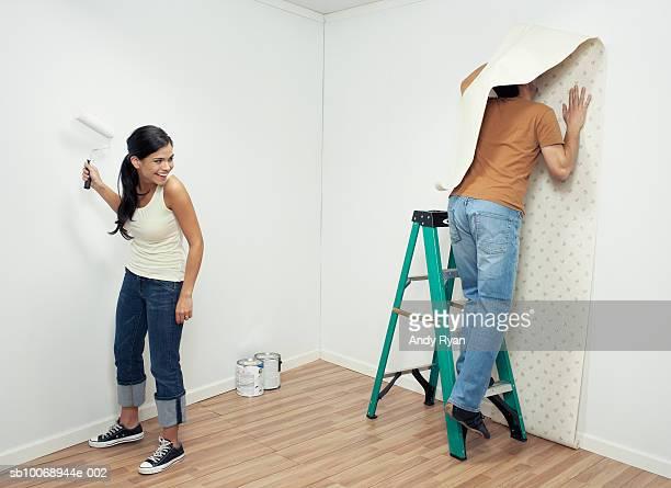 woman watching man hang wallpaper in room - clumsy stockfoto's en -beelden